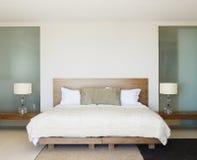 Σύγχρονη κρεβατοκάμαρα με το ξύλινο κρεβάτι Στοκ Εικόνες