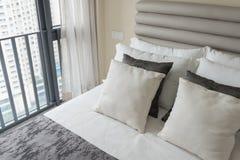 σύγχρονη κρεβατοκάμαρα με το σύνολο μαξιλαριών στο άσπρο κρεβάτι Στοκ Εικόνα