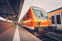 Σύγχρονη κόκκινη αμαξοστοιχία περιφερειακού σιδηροδρόμου υψηλής ταχύτητας στο ζωηρόχρωμο ηλιοβασίλεμα Στοκ Εικόνα