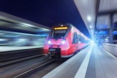 Σύγχρονη κόκκινη επιβατική αμαξοστοιχία υψηλής ταχύτητας τη νύχτα Στοκ Φωτογραφία