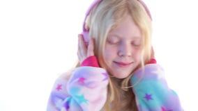 Σύγχρονη μόδα - το όμορφο ξανθό κορίτσι ακούει τη μουσική με τα ακουστικά και το χορό σε ένα άσπρο υπόβαθρο στο kigurumi φιλμ μικρού μήκους