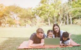 Σύγχρονη οικογένεια που χρησιμοποιεί το lap-top στηργμένος στο πάρκο στοκ εικόνα