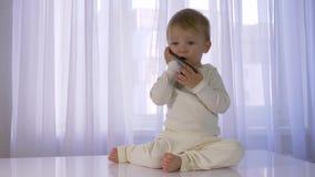 Σύγχρονη παιδική ηλικία, το καλό αστείο μωρό παίζεται και μιλώντας στο κινητό τηλέφωνο στο φωτεινό δωμάτιο φιλμ μικρού μήκους
