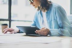 Σύγχρονη σοφίτα στούντιο διαδικασίας εργασίας Γυναίκα διευθυντή τέχνης που απασχολείται στον ξύλινο πίνακα με τη νέα ανεξάρτητη ί στοκ φωτογραφία με δικαίωμα ελεύθερης χρήσης