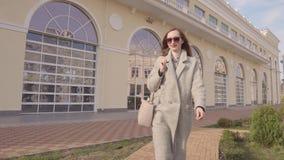 Σύγχρονη χαμογελώντας γυναίκα που περπατά έξω στα συμπαθητικά ενδύματα απόθεμα βίντεο