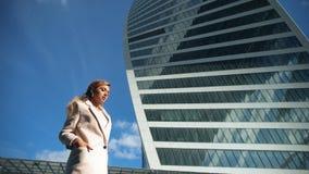 Σύγχρονοι ουρανοξύστες και πορτρέτο της νέας ελκυστικής επιχειρηματία φιλμ μικρού μήκους