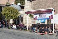 Σύγχρονοι τουρκικοί άνθρωποι που κάθονται στην οδό πριν από την τελετή προσευχής Στοκ Φωτογραφίες