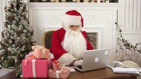 Σύγχρονος Άγιος Βασίλης που εργάζεται στο lap-top του και που προετοιμάζεται παρουσιάζει απόθεμα βίντεο