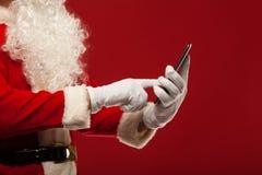Σύγχρονος Άγιος Βασίλης που χρησιμοποιεί το PC ταμπλετών πέρα από το κόκκινο Στοκ Εικόνες