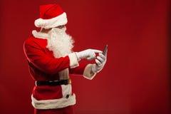 Σύγχρονος Άγιος Βασίλης που χρησιμοποιεί το PC ταμπλετών πέρα από το κόκκινο Στοκ φωτογραφία με δικαίωμα ελεύθερης χρήσης