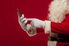 Σύγχρονος Άγιος Βασίλης που χρησιμοποιεί το PC ταμπλετών πέρα από το κόκκινο υπόβαθρο Christma Στοκ εικόνες με δικαίωμα ελεύθερης χρήσης
