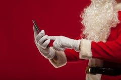 Σύγχρονος Άγιος Βασίλης που χρησιμοποιεί το PC ταμπλετών πέρα από το κόκκινο υπόβαθρο Christma Στοκ φωτογραφία με δικαίωμα ελεύθερης χρήσης