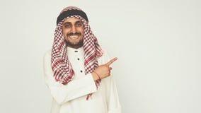 Σύγχρονος Άραβας στο γραφείο Ένα άτομο στο εθνικό φόρεμα χαμογελά και δείχνει το δάχτυλό του την ανώτερη δεξιά γωνία συγκινήσεις φιλμ μικρού μήκους