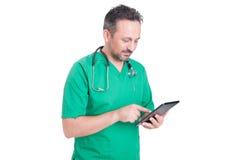 Σύγχρονος γιατρός που κοιτάζει βιαστικά Διαδίκτυο με την ασύρματη ταμπλέτα Στοκ εικόνες με δικαίωμα ελεύθερης χρήσης