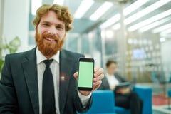 Σύγχρονος επιχειρηματίας που παρουσιάζει κινητό App Στοκ φωτογραφία με δικαίωμα ελεύθερης χρήσης