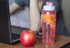 Σύγχρονος θηλυκός εργασιακός χώρος με το lap-top και το αποτοξινώνοντας νερό και τη Apple Στοκ Φωτογραφίες