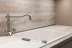 Σύγχρονος κρουνός χρωμίου σχεδιαστών πέρα από τον άσπρο νεροχύτη κουζινών Στοκ Φωτογραφίες