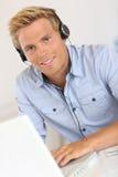 Σύγχρονος νέος εργαζόμενος που χρησιμοποιεί τα ακουστικά Στοκ Φωτογραφία