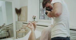 Σύγχρονος νέος τύπος κρεβατοκάμαρων που κάνει κάποια φωτογραφία για τη φίλη του στο κρεβάτι, είναι πολύ χαρισματική, θέτοντας μπρ απόθεμα βίντεο