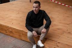 Σύγχρονος νεαρός άνδρας στα άσπρα μοντέρνα πάνινα παπούτσια δέρματος στο καθιερώνον τη μόδα μπεζ παντελόνι σε ένα μαύρο εκλεκτής  στοκ φωτογραφία