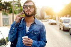 Σύγχρονος νεαρός άνδρας με το κινητό τηλέφωνο στην οδό Στοκ Εικόνα