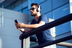 Σύγχρονος νεαρός άνδρας που ακούει τη μουσική με το κινητό τηλέφωνο στο στρεπτόκοκκο Στοκ Εικόνα