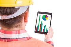 Σύγχρονος οικοδόμος ή εργάτης οικοδομών που ελέγχει τα διαγράμματα στην ταμπλέτα Στοκ Φωτογραφίες