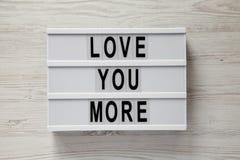 """Σύγχρονος πίνακας με το κείμενο """"αγάπη εσείς περισσότεροι """"σε ένα άσπρο ξύλινο υπόβαθρο, τοπ άποψη Βαλεντίνος ` s ημέρα στις 14 Φ στοκ φωτογραφίες"""