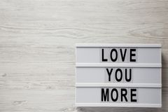 """Σύγχρονος πίνακας με το κείμενο """"αγάπη εσείς περισσότεροι """"σε μια άσπρη ξύλινη επιφάνεια Βαλεντίνος ` s ημέρα στις 14 Φεβρουαρίου στοκ εικόνα"""