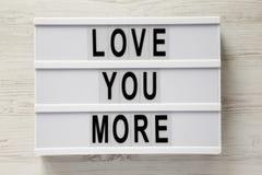 """Σύγχρονος πίνακας με το κείμενο """"αγάπη εσείς περισσότεροι """"σε μια άσπρη ξύλινη επιφάνεια, τοπ άποψη Επίπεδος βάλτε, γενικά έξοδα, στοκ εικόνες"""