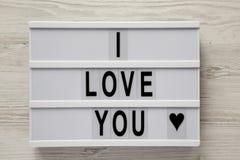 """Σύγχρονος πίνακας με το κείμενο """"σ' αγαπώ """"σε ένα άσπρο ξύλινο υπόβαθρο, τοπ άποψη Επίπεδος βάλτε, γενικά έξοδα Βαλεντίνος ` s ημ στοκ φωτογραφίες"""