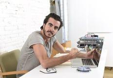Σύγχρονος σπουδαστής ή επιχειρηματίας ύφους hipster που εργάζεται στην πίεση με γραφείων lap-top στο σπίτι που ανατρέπεται Στοκ φωτογραφίες με δικαίωμα ελεύθερης χρήσης