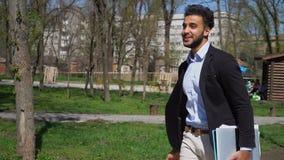 Σύγχρονος σπουδαστής που περπατά στο πάρκο με το lap-top διαθέσιμο απόθεμα βίντεο