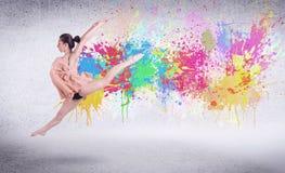 Σύγχρονος χορευτής οδών που πηδά με τους ζωηρόχρωμους παφλασμούς χρωμάτων Στοκ Φωτογραφίες