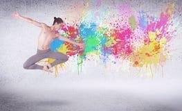 Σύγχρονος χορευτής οδών που πηδά με τους ζωηρόχρωμους παφλασμούς χρωμάτων Στοκ φωτογραφία με δικαίωμα ελεύθερης χρήσης