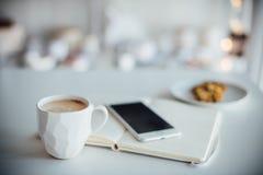 Σύγχρονο άσπρο γραφείο, χειροποίητο φλιτζάνι του καφέ σχεδιαστών, smartphone στοκ φωτογραφίες