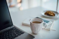 Σύγχρονο άσπρο γραφείο, χειροποίητο φλυτζάνι σχεδιαστών με τον καφέ, smartpho στοκ εικόνες