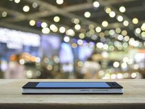 Σύγχρονο έξυπνο τηλέφωνο με την κενή μπλε οθόνη στον ξύλινο πίνακα μέσα για Στοκ Φωτογραφία