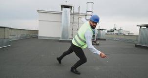 Σύγχρονο εργοτάξιο οικοδομής που χαμογελά τον ελκυστικό χορεύοντας αρχιτέκτονα που απολαμβάνει τη στιγμή στη στέγη της οικοδόμηση απόθεμα βίντεο