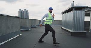 Σύγχρονο εργοτάξιο οικοδομής στο χαρισματικό αρχιτέκτονα ή το μηχανικό στεγών με έναν χορό κρανών ασφάλειας που διεγείρεται στο μ απόθεμα βίντεο