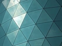Σύγχρονο εταιρικό κτήριο με τα γωνιακά διαμορφωμένα αντανακλημένα πλακάκια παραθύρων που απεικονίζουν τον ουρανό και τα σύννεφα στοκ εικόνες