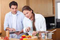 Σύγχρονο ζεύγος που χρησιμοποιεί έναν υπολογιστή ταμπλετών στο μάγειρα στοκ φωτογραφία