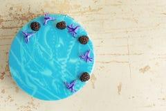 Σύγχρονο καθιερώνον τη μόδα mousse κέικ με το μπλε μαρμάρινο λούστρο καθρεφτών Ντεκόρ λουλουδιών και βατόμουρων Στοκ φωτογραφίες με δικαίωμα ελεύθερης χρήσης