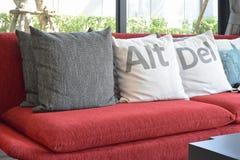 Σύγχρονο καθιστικό με τα μαξιλάρια στον κόκκινο καναπέ Στοκ εικόνες με δικαίωμα ελεύθερης χρήσης