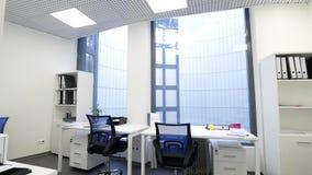 Σύγχρονο, κομψό γραφείο με τα πανοραμικά παράθυρα και εργασιακοί χώροι Ελαφρύ εσωτερικό γραφείων με τους πίνακες, τις καρέκλες κα απόθεμα βίντεο
