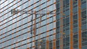 Σύγχρονο κτήριο με τον απεικονισμένους ουρανό γυαλιού παράθυρα και το γερανό οικοδόμησης Στοκ Εικόνα