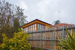 Σύγχρονο κτήριο τούβλου τα ξύλινα παράθυρα που περιβάλλονται με από το φράκτη Στοκ Εικόνες