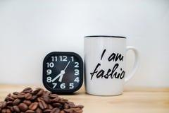 Σύγχρονο μαύρο ξυπνητήρι δίπλα στην κούπα καφέ στοκ φωτογραφίες