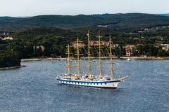 Σύγχρονο σκάφος με τους ιστούς και τα πανιά παρόμοιους με την παλαιά φρεγάτα Τοποθετημένος στη θάλασσα σε ένα υπόβαθρο του νησιού Στοκ φωτογραφία με δικαίωμα ελεύθερης χρήσης