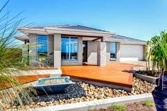 Σύγχρονο σπίτι με τα δέντρα και τα στοιχεία διακοσμήσεων πετρών συμπεριλαμβανομένης μιας μικρής λίμνης νερού με το αμμοχάλικο και στοκ εικόνες με δικαίωμα ελεύθερης χρήσης
